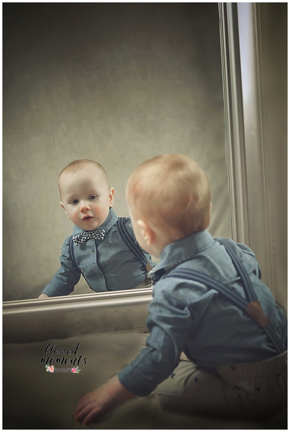 Photo of 1 year old boy looking at his reflection in the mirror.