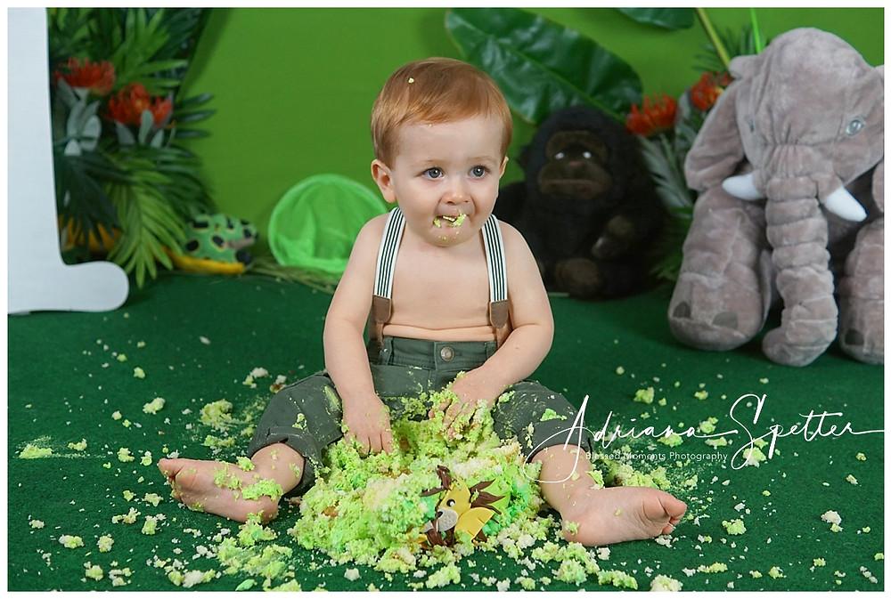 Little boy smashing his Safari theme cake