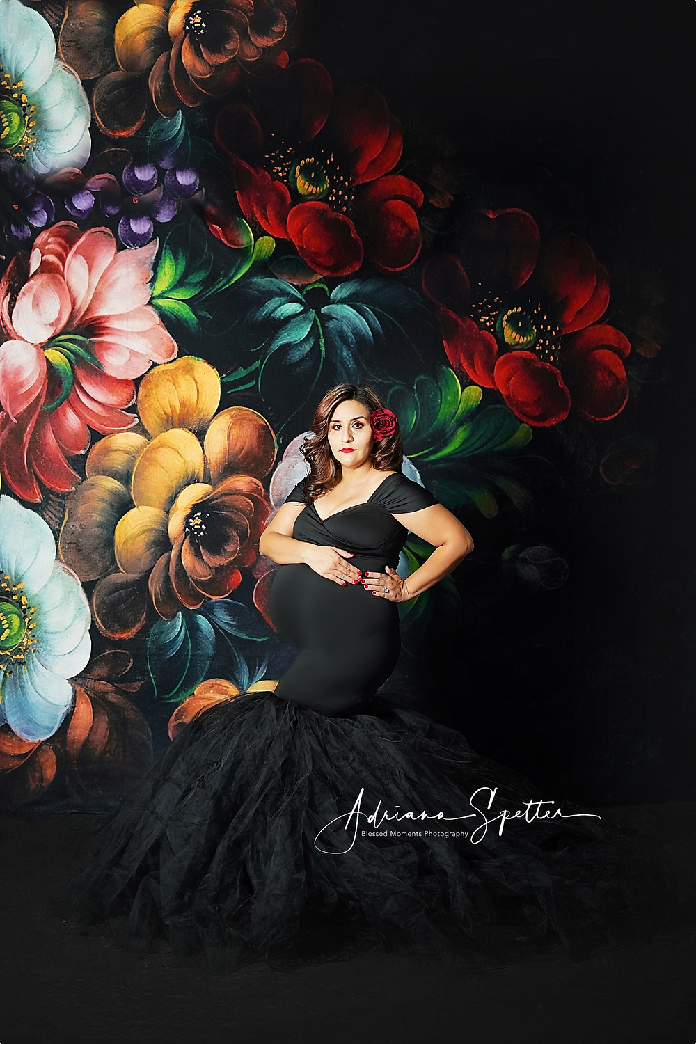 Studio maternity photo shot at Blessed Moments Photography Studio.  Mama is wearing a black tulie gown against a floral backdrop.