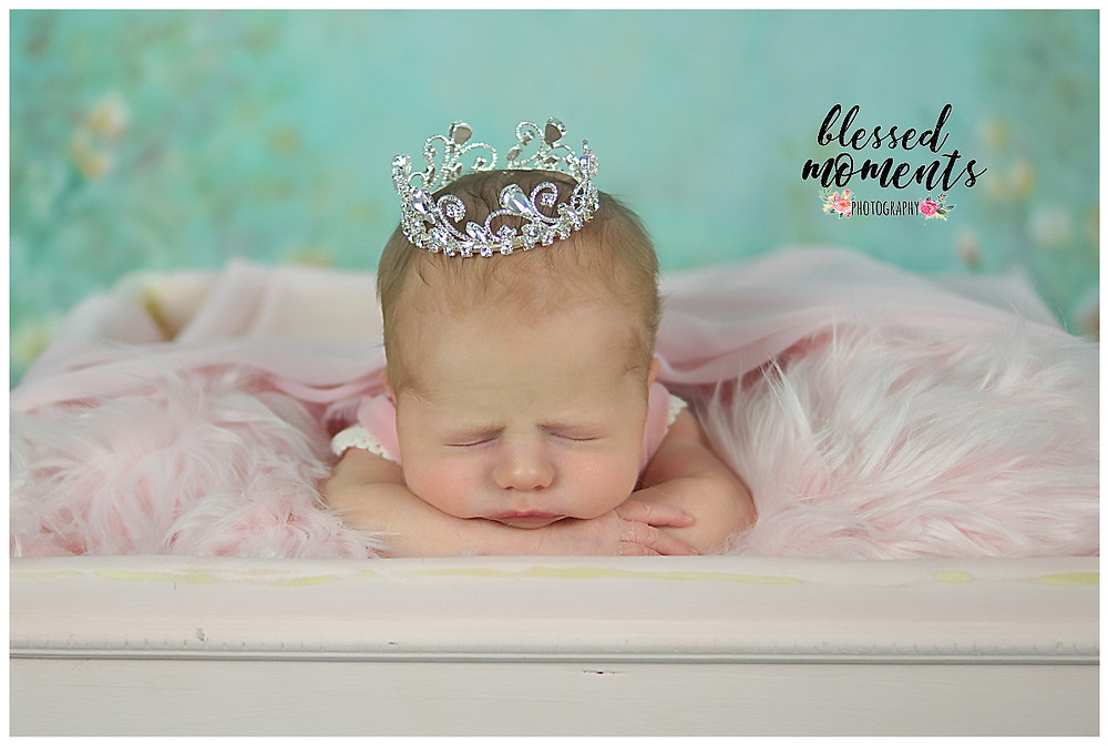 newborn baby girl wearing princess crown in a pink outfit