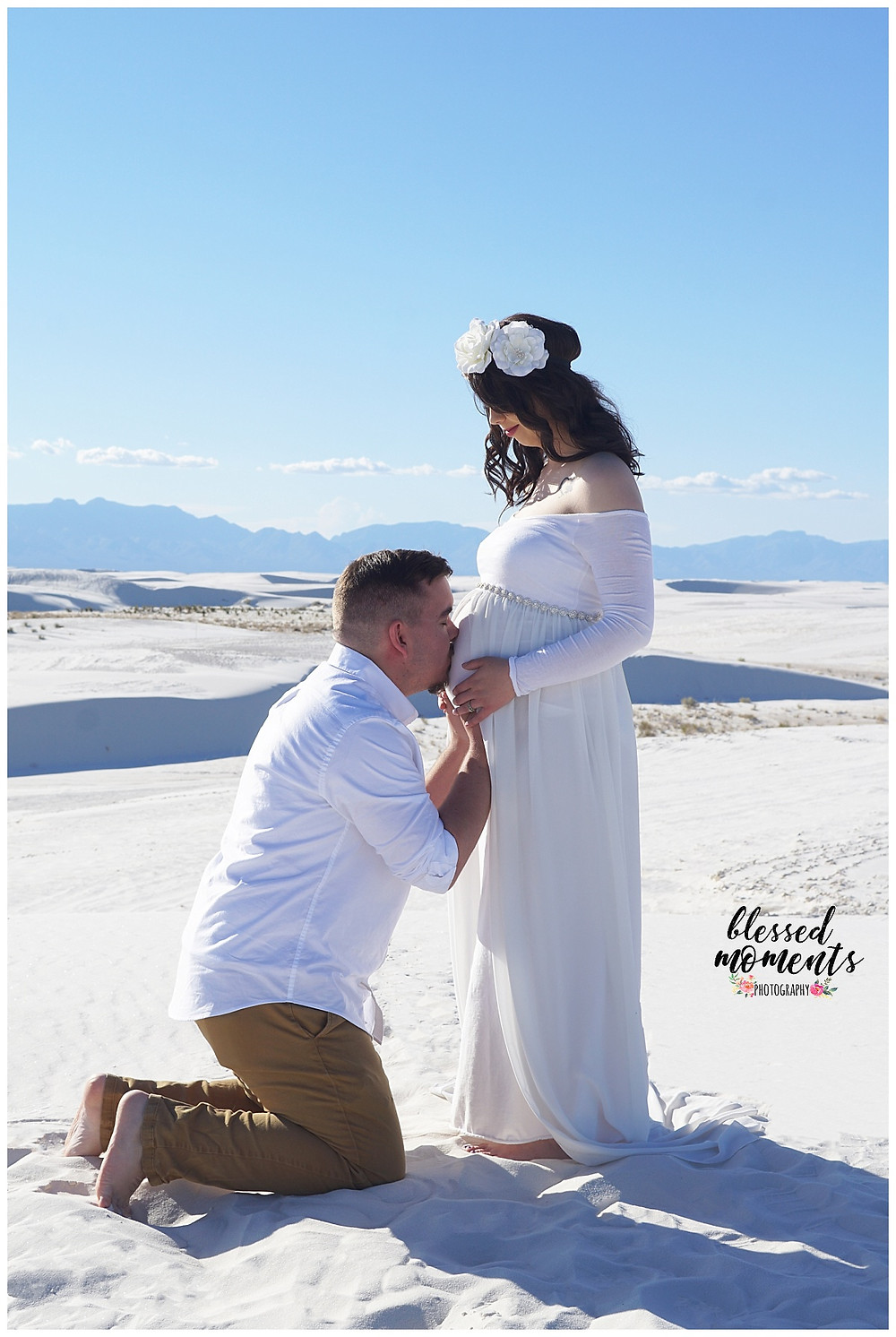 Proud papa kissing his wife's pregnant belly at White Sands