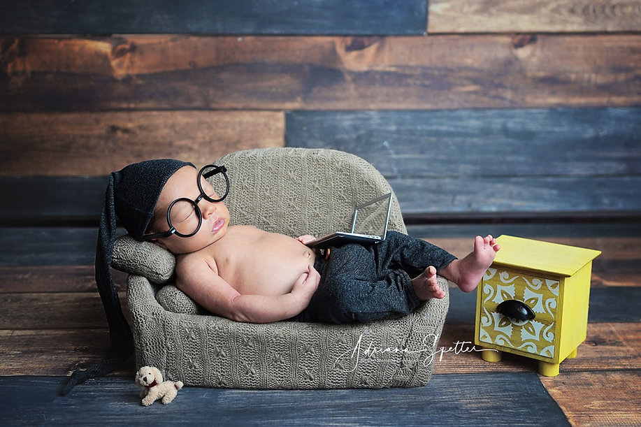 Hollomana newborn photographer with newborn boy wearing glasses sleeping on couch with his laptop