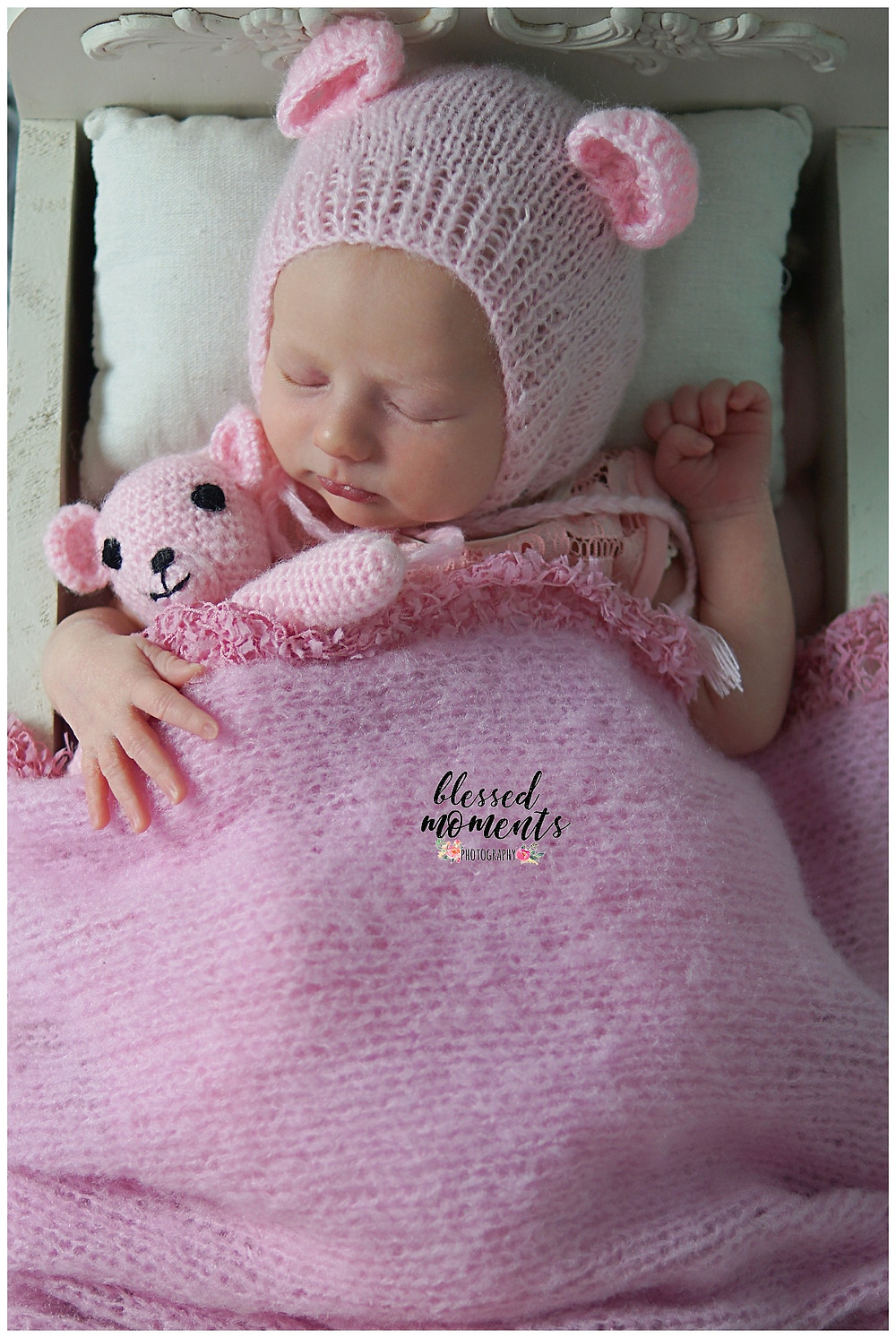 newborn baby girl in a little bed wearing a pink bear bonnet and holding a pink teddy bear.