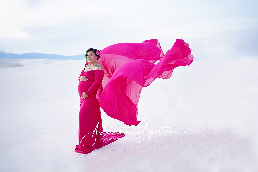 A candy pink maternity gown with mama wearing a pink flower in her hair.  Photo is taken at White Sands National Monument.