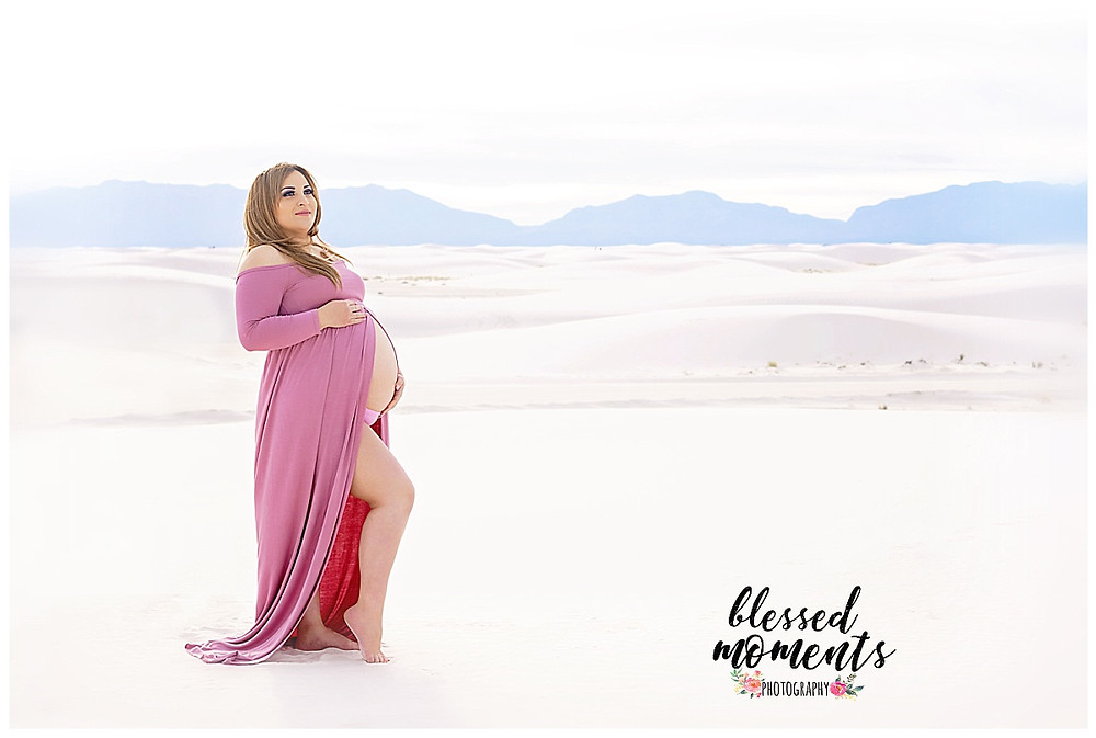 Maternity photo taken at White Sands National Monument wearing pink maternity gown.