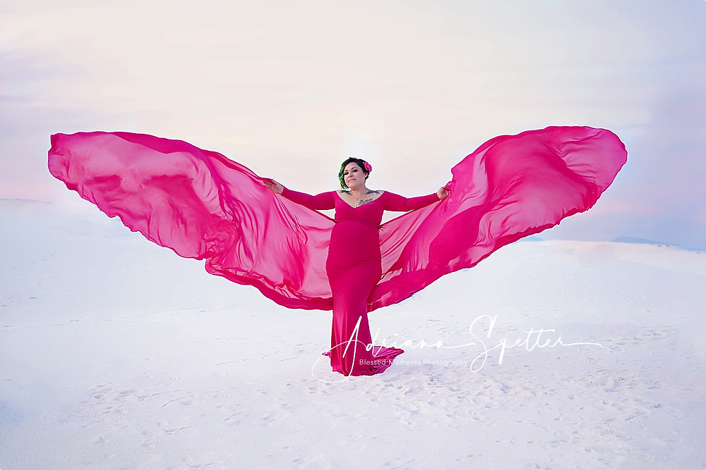 A maternity photo with a Candy Pink maternity gown with a butterfly tail spread open in the air looking like butterfly wings at White Sands National Monument.