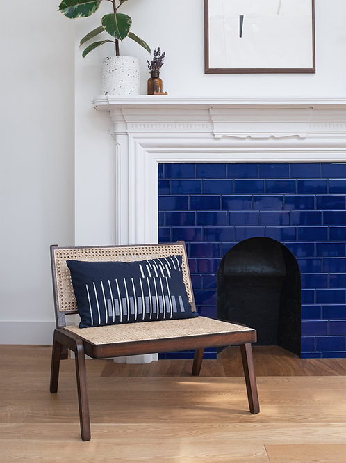Blue decorative cushion on a wooden armchair in front of a blue fireplace