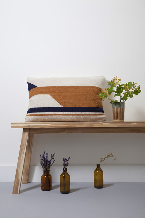 100% wool sourced naturally hand-dyed Large Convergent Cushion Mostaza on a table next to a plant