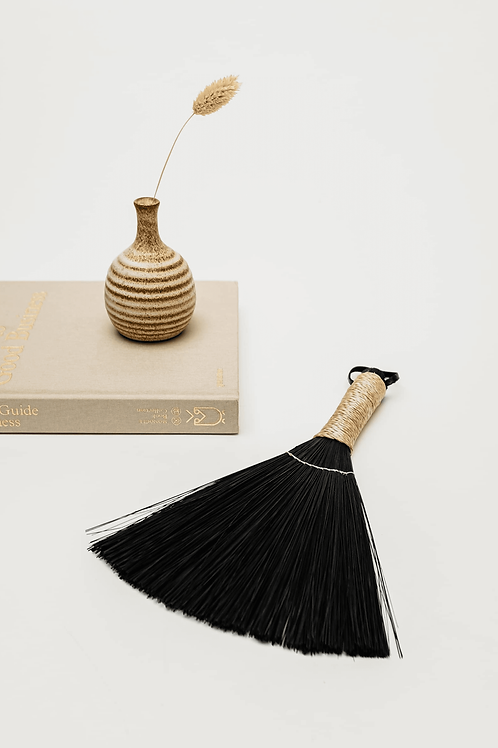 Black Buri Buri Hand Whisk Broom on table next to book