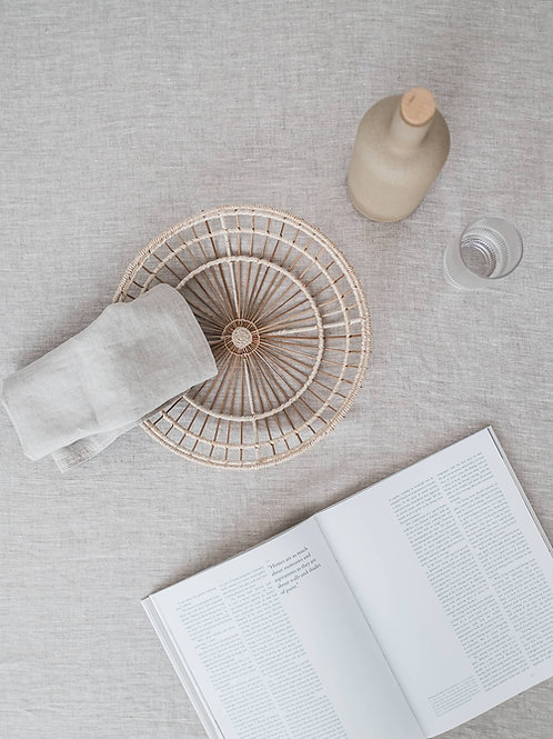 Woven tray on tabletop next to book and bottle