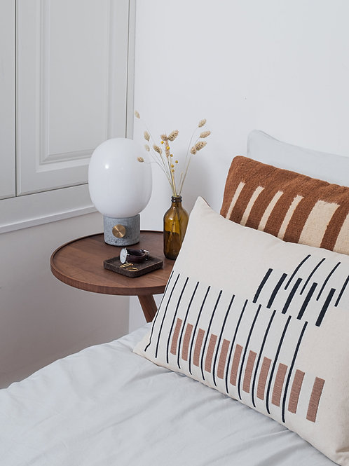 100% cotton contemporary handmade stripe Parallel Cushion Off White on a bed next to a side table
