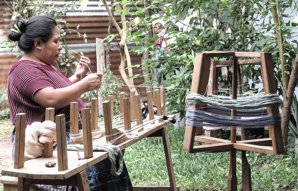 artisan preparing backstrap weaving in a garden in Guatemala