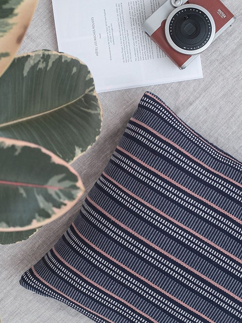Handwoven Linear Cushion Navy on linen with plant and camera