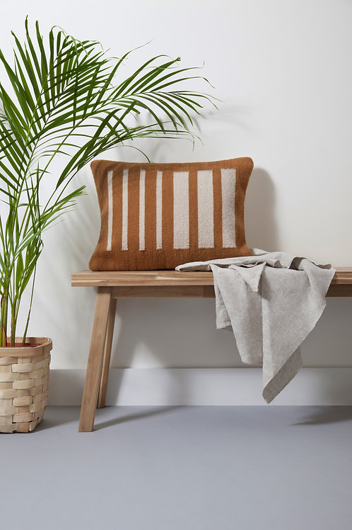 brown coloured Pilotis Cushion Mostaza on a bench with a plant next to it