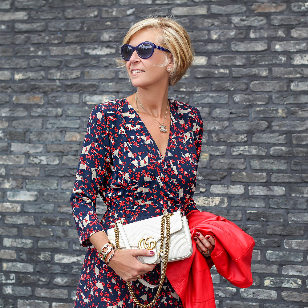 Woman wearing a printed midi dress in navy with red and ivory accent.