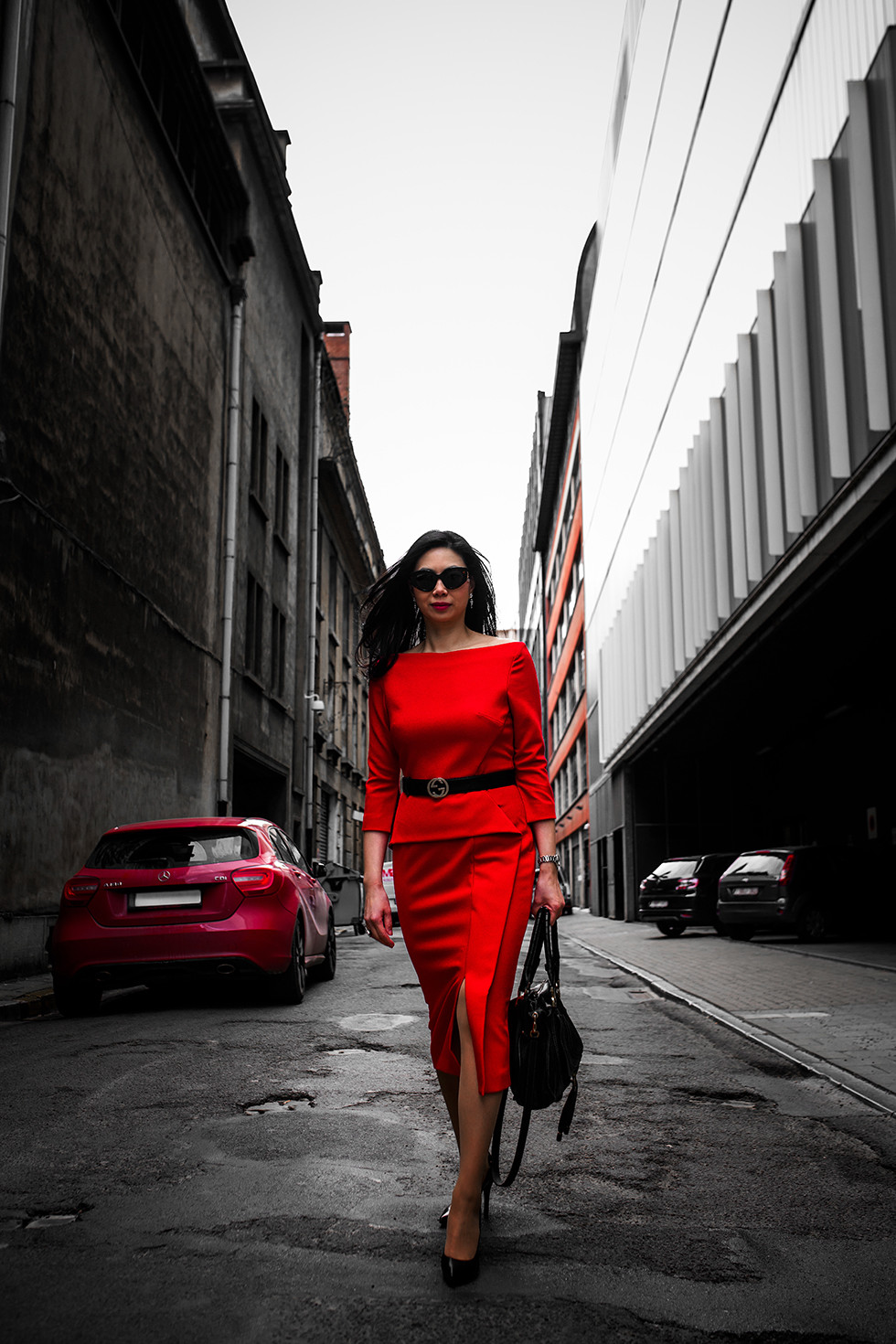 Business women in a stree wearing a red pencil dress with black leather accessoires.