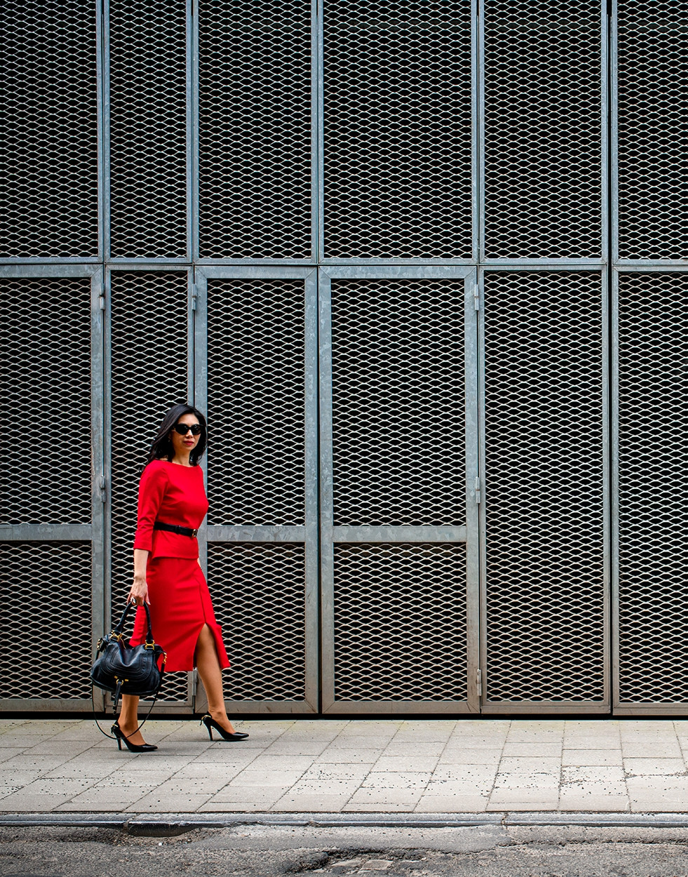 Woman in a red pencil dress walking in the street