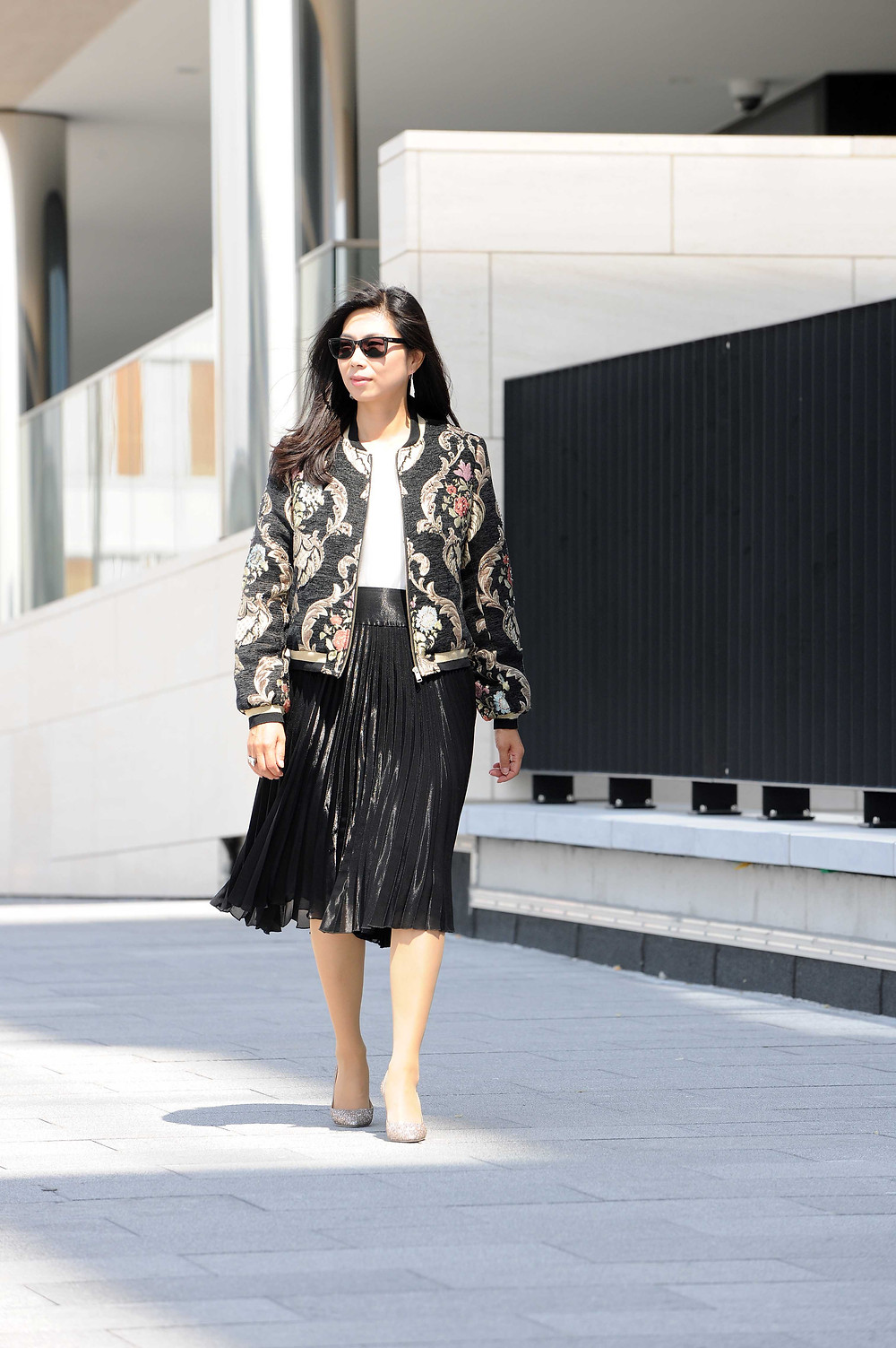 Jacquard floral bomber jacket with a black metallic pleated skirt