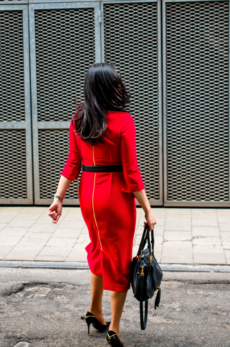Woman wearing a red pencil dress turning her back