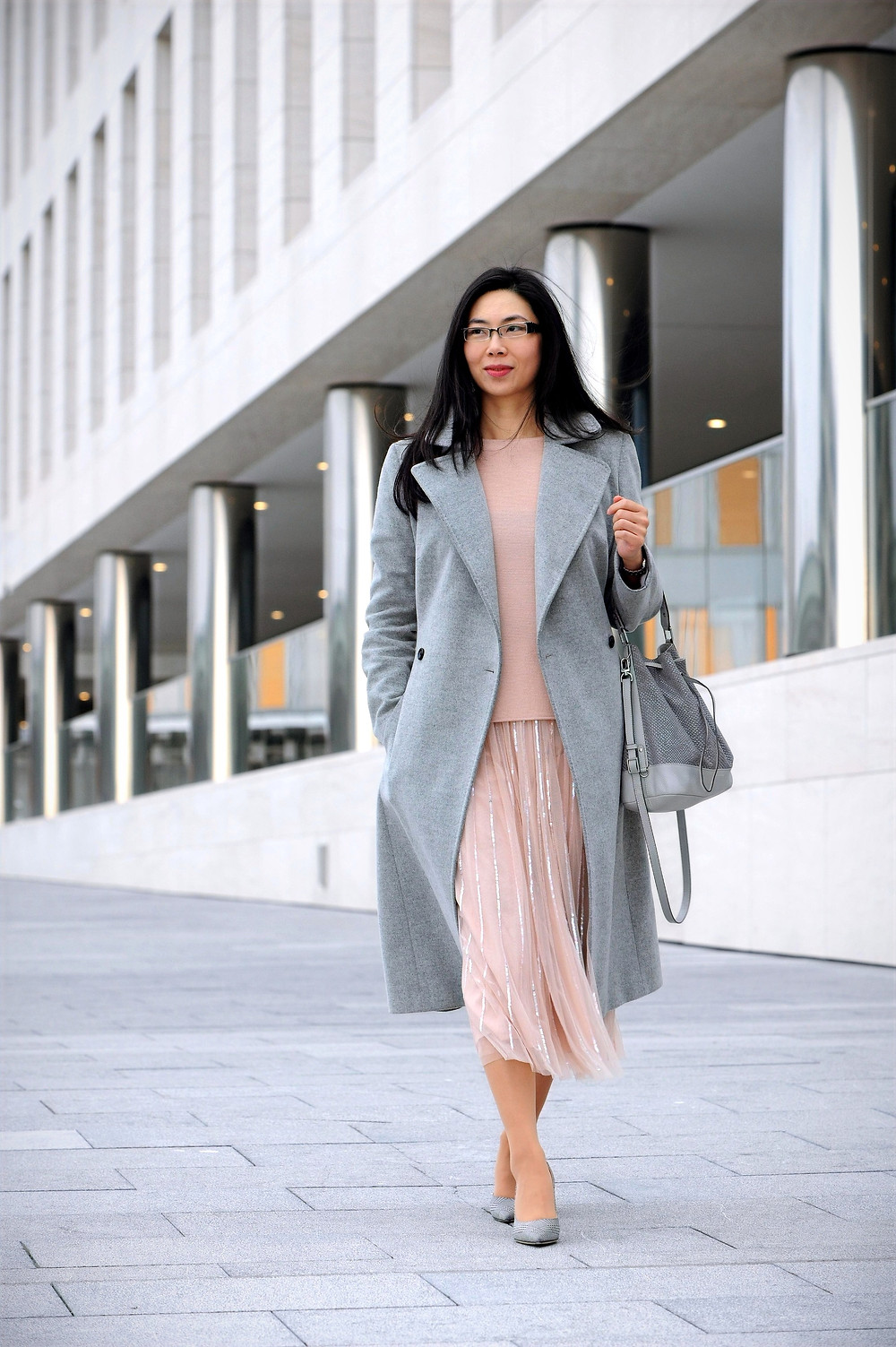 Business casual woman outfit rose quartz tulle skirt and light grey Karen Millen wool coat.