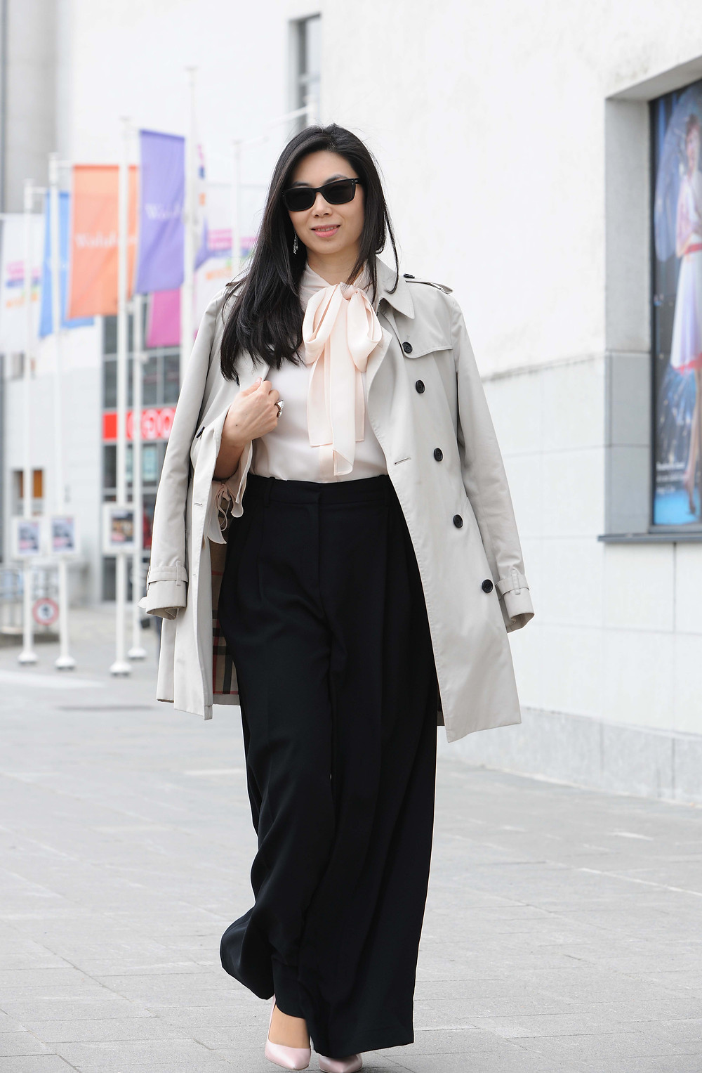 Trench coat wiht a pussy bow blouse and wide-leg black pants.