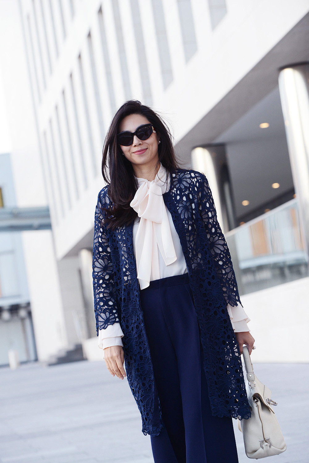 Business Formal woman outfit with a navy floral lace coat and a navy pants from Roland Mouret.