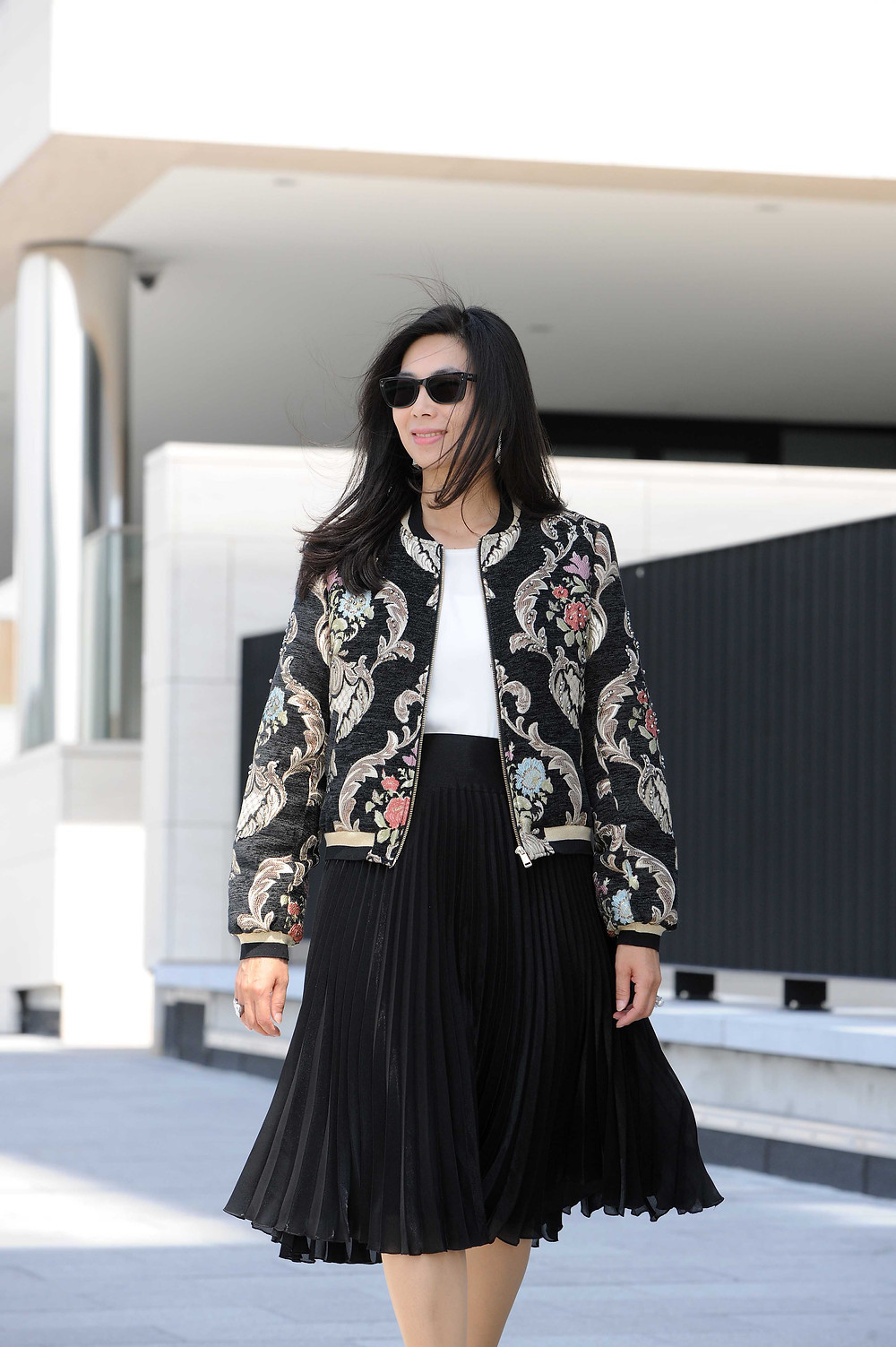 Business Casual woman outfit with a floral bomber jacket and black pleated skirt from Karen Millen