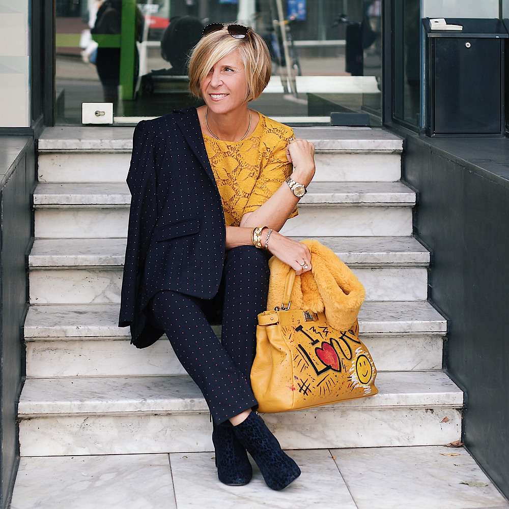 Woman wearing a navy business suit with yellow top and bag.