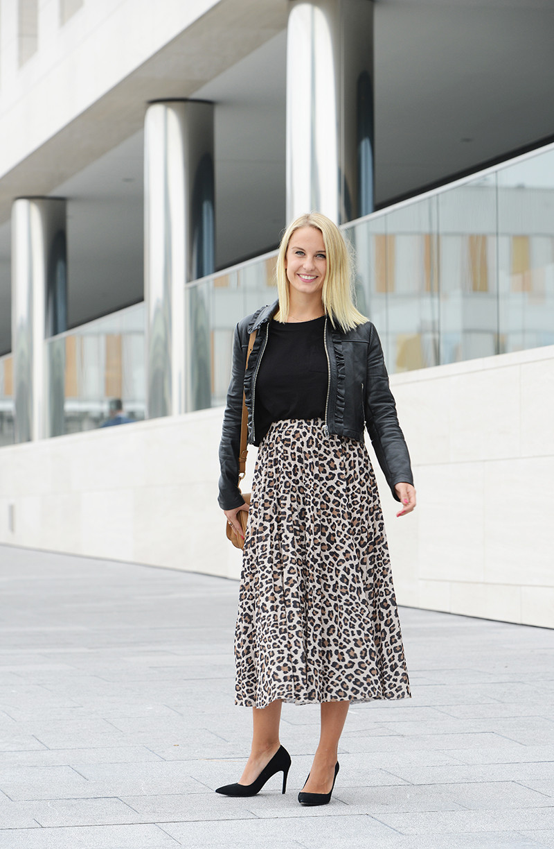 Young business woman wearing a midi leopard print skirt with black leather jacket and pumps.