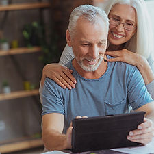 retired-couple-looking-at-tablet-in-home
