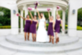 bride and bridesmaids pose with bouquets held high