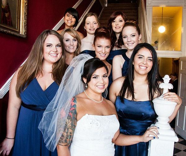bride and bridesmaids pose wedding stairs