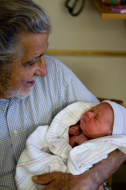 Great grandpa holding newborn baby grandson after birth