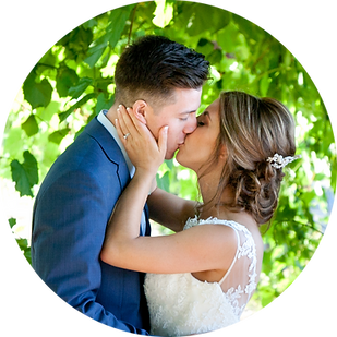 Bride and groom kissing under grape vines in vineyard