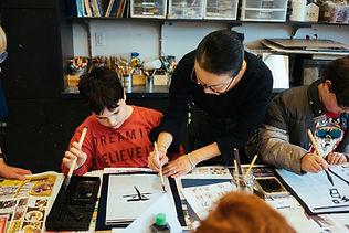 teacher instructing student on caligraphy