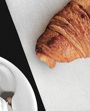 Tovagliolo di carta bianco con brioches e tazza di caffè