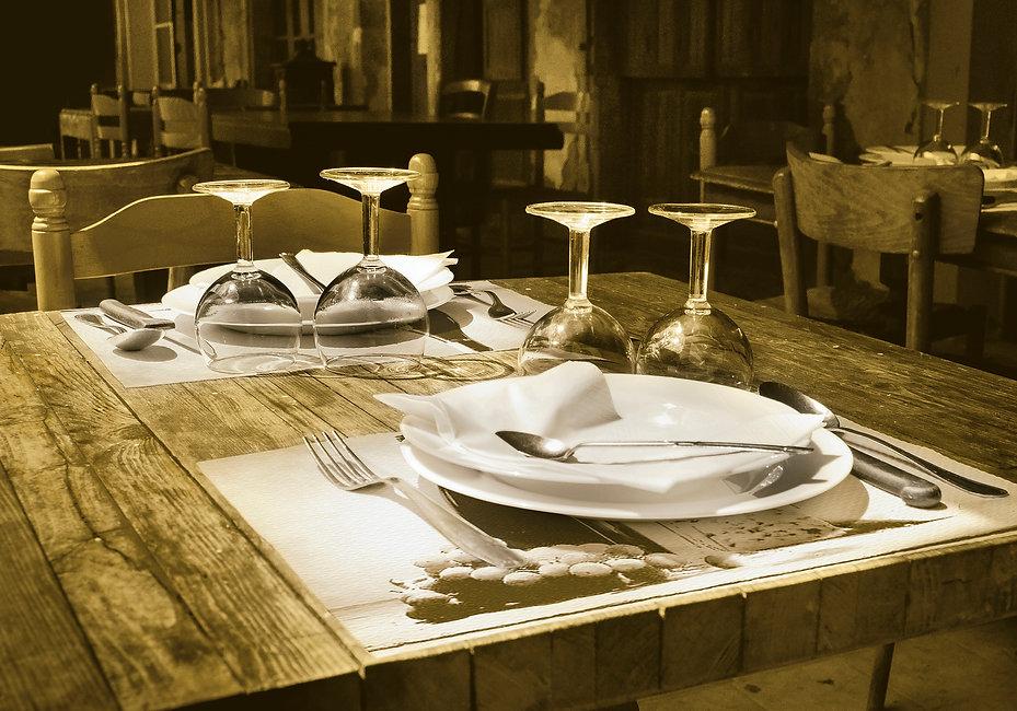 Tovagliette in carta bianca ambientate su tavolo di legno con posate, piatti, tovaglioli e bicchieri