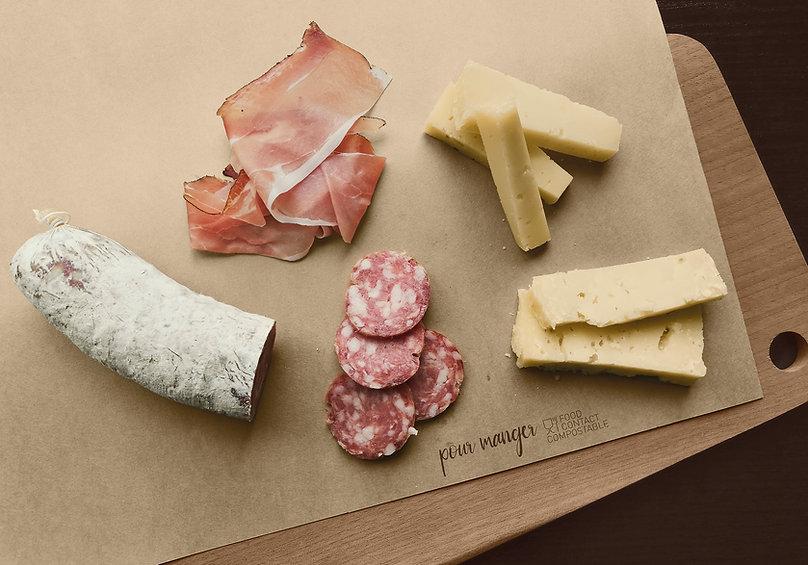 Tovaglietta in carta alimentare Pour Manger posizionata su tagliere con formaggio e salame