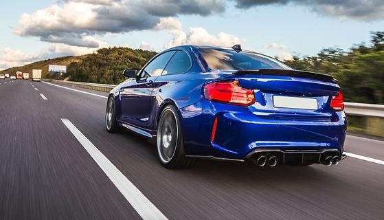 back-view-of-blue-sedan-on-the-road 2.jp