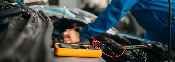 car-repairman-with-multimeter-battery-in