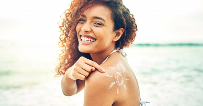 young-woman-smiling-applying-sunscreen-1