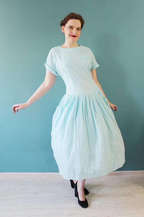 Lata osiemdziesiąte - dłuższa błękitna sukienka ze złotymi guzikami na plecach