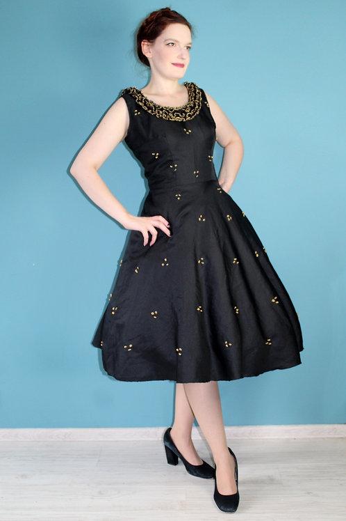 Lata sześćdziesiąte - rozkloszowana sukienka koktajlowa czarna złote ozdoby