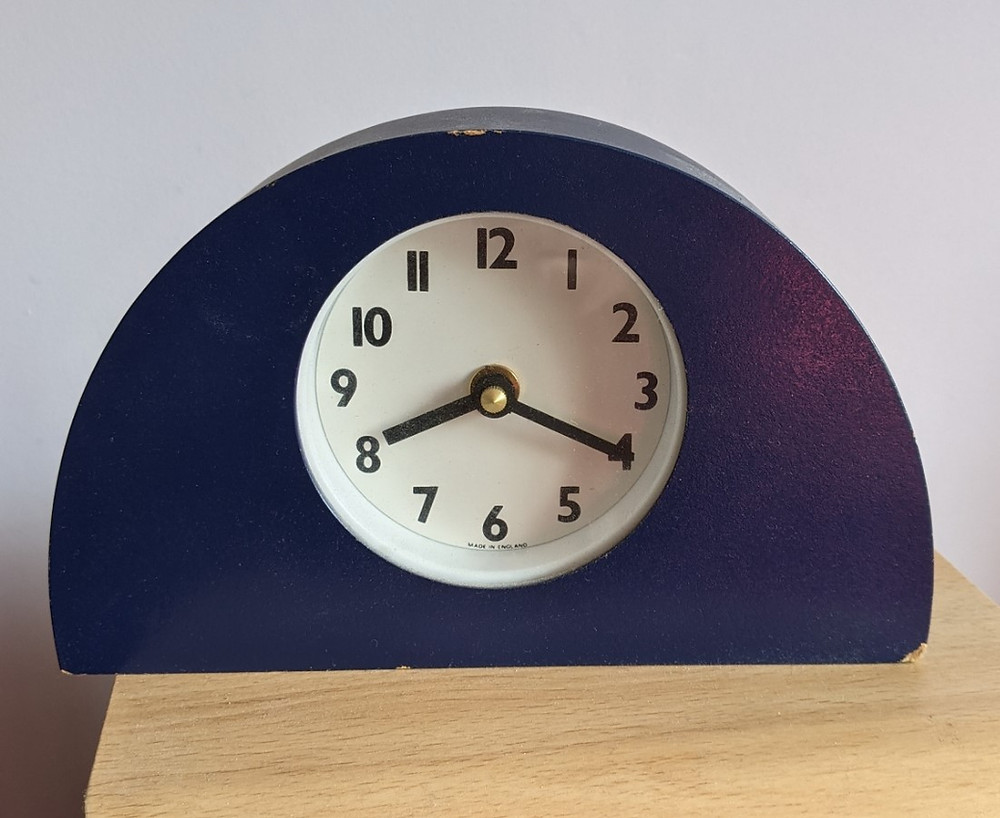 Small analogue clock in a semi-circular blue mount showing the time as 8.20