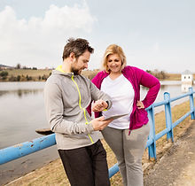 Personal trainer checking stopwatch and talking to woman.jpg