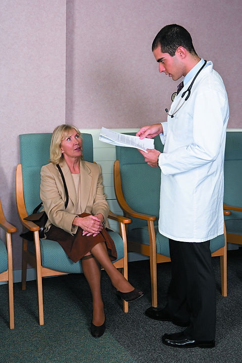 Standing doctor talking to a seated woman.jpg