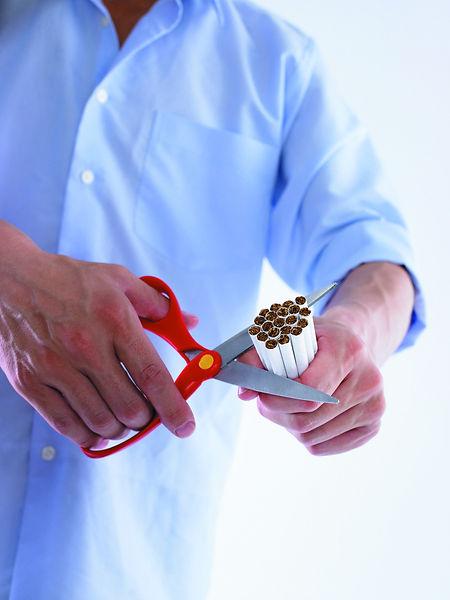 Man cutting cigarettes in half.jpg