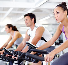A man and two women on exercise bikes.jpg