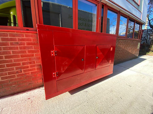 A red metal cabinet attached to the exterior of a building.jpg