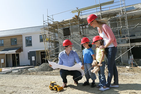 Man showing woman and two children plans on a building site.jpg